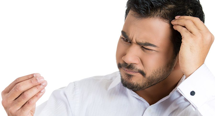 Man staring at hair that he appears to have pulled out
